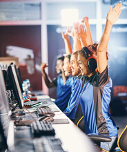 Winning. Young Multiracial Team Of Happy Professional Cyber Sport Gamers Celebrating Success, Raising Hands Up While Participating In ESports Tournament