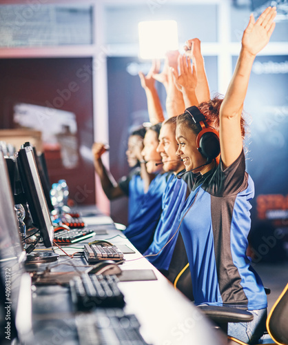 Obraz Winning. Young multiracial team of happy professional cyber sport gamers celebrating success, raising hands up while participating in eSports tournament - fototapety do salonu