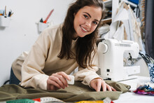 Portrait Of Happy Seamstress Sewing In The Workshop