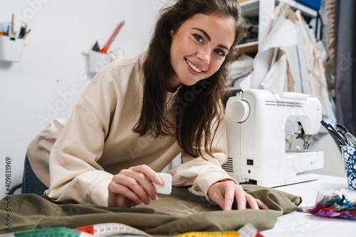 Fototapeta Portrait of happy seamstress sewing in the workshop