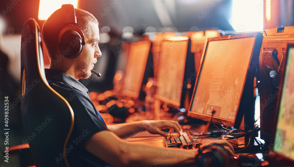 Fototapeta Side view of a focused male professional gamer wearing headphones participating in eSport tournament, looking at PC screen and playing online video game