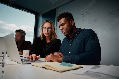 Photo Two diverse business people working on project together using laptop in the offi