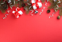 Flat Lay Composition With Serpentine Streamers And Christmas Decor On Red Background. Space For Text