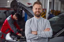 Confident Customer Near Mechanic Fixing Car