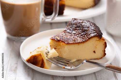 Fototapeta Delicious basque cheesecake portion with a coffee