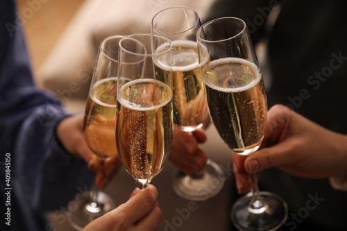 Foto People clinking glasses with champagne at home, closeup