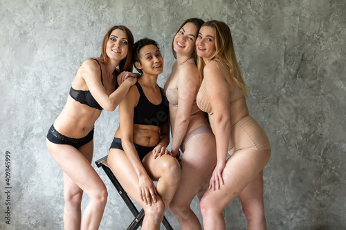 Obraz friendship, beauty, body positive and people concept - group of happy women different in underwear over gray background - fototapety do salonu