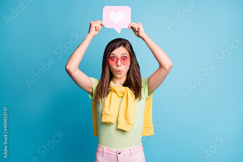 Obraz Photo of pretty person hold heart paper above head pink sunglass tied on shoulders sweater isolated on blue color background - fototapety do salonu