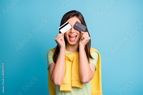 Obraz Photo of young attractive pretty crazy excited smiling girl cover eyes with two credit cards isolated on blue color background - fototapety do salonu