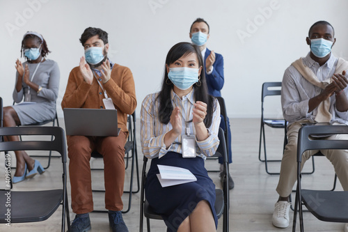Canvas Print Multi-ethnic group of business people wearing masks and applauding with social d
