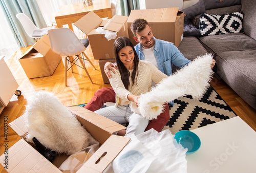Obraz na plátně Smiling young couple move into a new home sitting on floor and unpacking boxes of their belongings