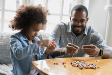 Close Up Smiling African American Father And Little Daughter Playing With Colorful Beads, Sitting On Couch At Home, Crafting Bracelet, Family Involved In Creative Activity, Enjoying Leisure Time