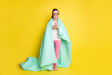 Full Length Photo Of Sweet Woman Dressed Nightwear Covering Duvet Holding Modern Device Isolated Yellow Color Background