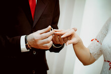 The Groom Puts The Ring On The Bride's Hand. Hands Of The Newlyweds On The Wedding Day, Close-up. The Exchange Of Rings During The Marriage.