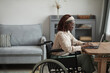 Leinwandbild Motiv Side view portrait of young African-American woman using wheelchair while working from home in minimal grey interior, copy space