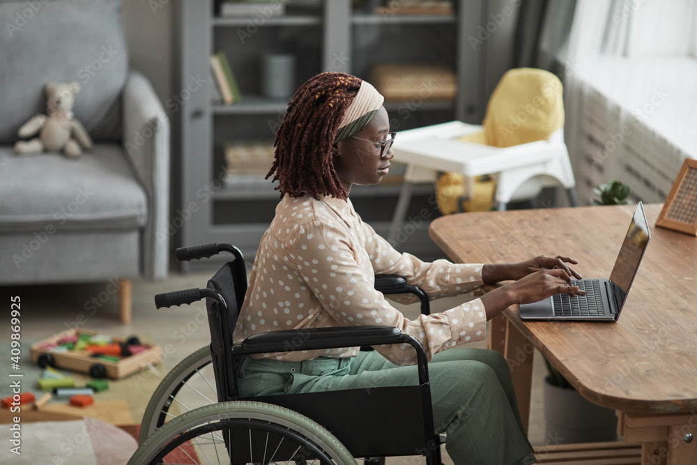 Fototapeta High angle portrait of young African-American woman using wheelchair while working from home with childrens toys in background, copy space