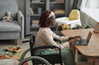 High angle portrait of young African-American woman using wheelchair while working from home with childrens toys in background, copy space