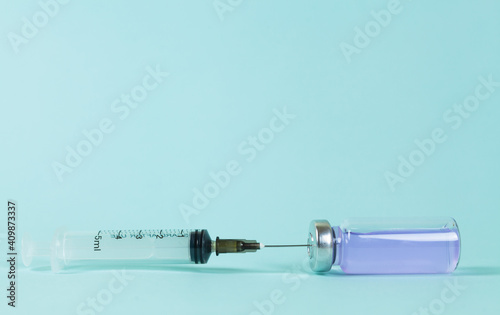 Canvas Print Covid-19 Recorded vaccine bottle with liquid and extracting vaccine from it with a syringe on a blue background