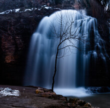 Closeup Shot Of A Waterfall In Rocks Surrounded By Bare Trees On An Autumn Day