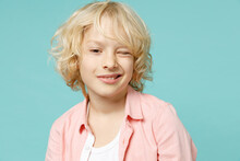 Funny Cheerful Little Curly Kid Boy 10s Years Old Wearing Pastel Pink Shirt Blinking Looking Camera Isolated On Blue Turquoise Color Background Children Studio Portrait. Childhood Lifestyle Concept.