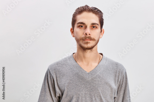 Obraz People concept - bearded face man. Friendly young man in gray shirt look in to the camera over grey background. Copy space - fototapety do salonu