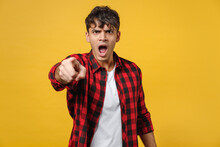 Young Spanish Latinos Indignant Stylish Fashionable Angry Man 20s In Red Checkered Shirt, White T-shirt Point Index Finger Camera On You Scream Shout Isolated On Yellow Background Studio Portrait.