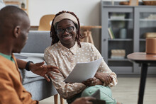 Portrait Of Modern African-American Couple Working From Home Together, Focus On Smiling Young Woman Holding Document While Sitting On Floor, Copy Space