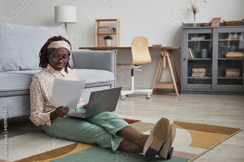 Obraz Full length portrait of modern African-American woman working from home while sitting on floor on graphic carpet and using laptop, copy space - fototapety do salonu