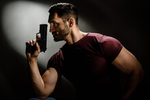 Serious Hollywood Styled Film Actor Holding Gun Like Secret Agent