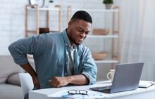African Guy Having Backache Massaging Aching Back At Workplace Indoor