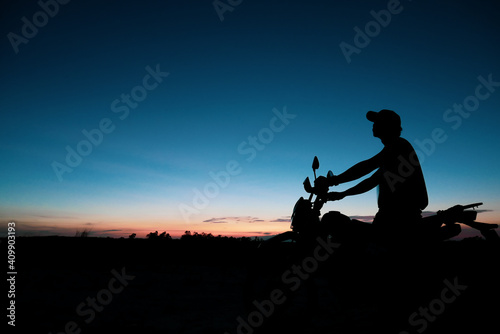 Obraz Silhouette of a man wearing a hat with an Off-road motorbike In the evening - fototapety do salonu