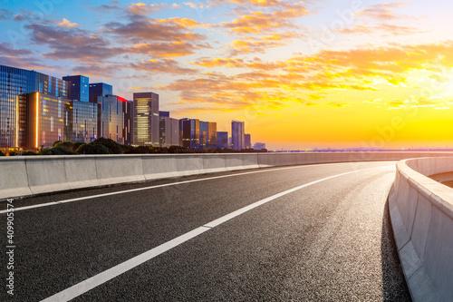 Empty asphalt road and modern city skyline in Hangzhou at sunrise,China.