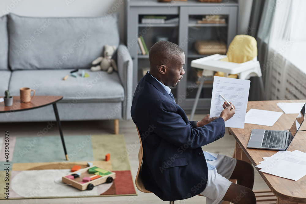 Fototapeta High angle portrait of African-American man wearing formal jacket and shorts during online meeting while working from home, copy space
