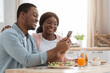 Cheerful black couple using smartphone while having breakfast in cozy kitchen