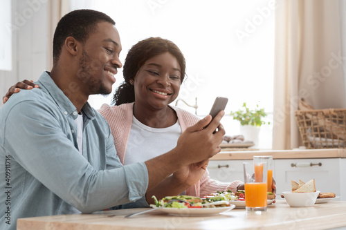 Cheerful black couple using smartphone while having breakfast in cozy kitchen Wallpaper Mural