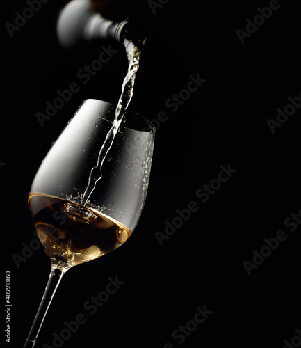 Fotografía Pouring white wine in a glass goblet.