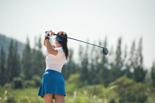 Woman Golfer Finished Golf Swing. Close Up Of Female Golf Player Swinging Golf Club On Fairway During Day Time.