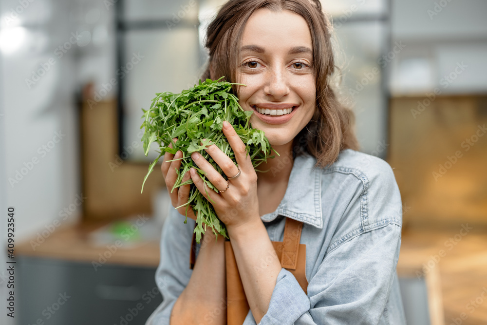 Fototapeta Portrait of pretty smiling woman in apron with fresh arugula on the kitchen. Healthy cooking concept. Close up. High quality photo