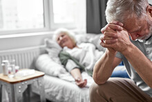 Elderly Man Crying And Mourning The Loss Of His Wife, Sitting By Her Side. Focus On Upset Man Looking Down. Coronavirus, Covid-19 Concept