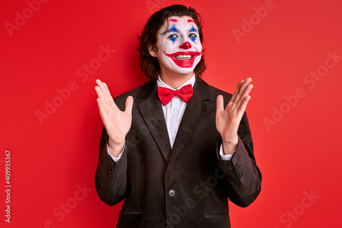 Fotografia ugly clown man wearing black suit costume and halloween makeup grimacing making performance, isolated over red background