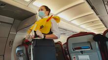 Woman Stewardess Flight Attendant In Face Mask Presenting Life Vest On Board Before The Flight Departure