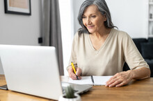 Charming Mature Mid-aged Woman Watching Online Webinars On The Laptop Sitting At The Table At Home, Taking Notes, E-learning. Senior Business Lady Researching, Analyzing Tasks Works In The Home Office