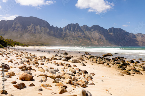 Beautiful beach by the sea and mountains with rocks and sand on a sunny day