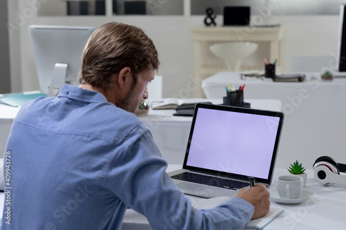 Caucasian businessman sitting at desk using laptop in an empty office