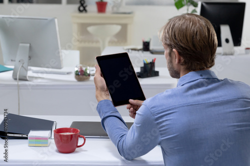 Rear view of caucasian businessman sitting at desk making video call using tabet