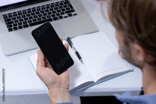 Over shoulder view of caucasian businessman sitting at desk making video call using smartphone