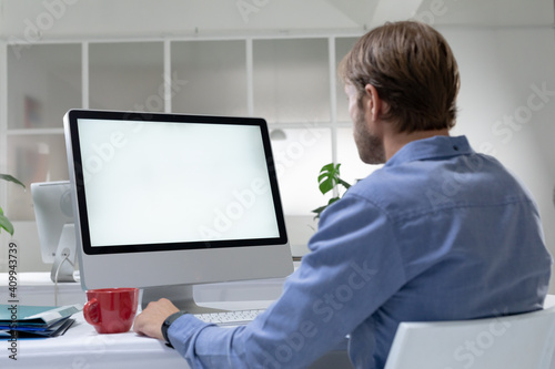 Rear view of caucasian businessman sitting at desk making video call using desktop computer