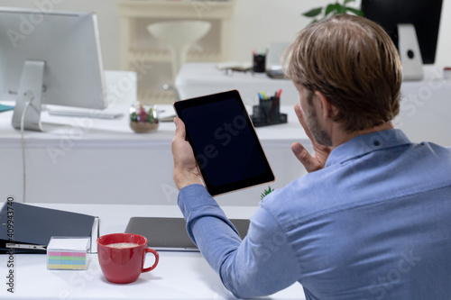 Rear view of caucasian businessman sitting at desk waving making video call using tabet