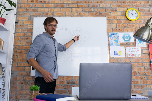 Caucasian male teacher giving online lesson using laptop standing talking at whiteboard