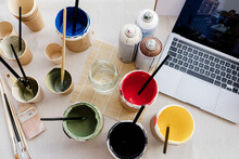 From Above Of Set Of Paints Of Various Colors And Paintbrushes Arranged With Laptop On Table In Creative Art Studio
